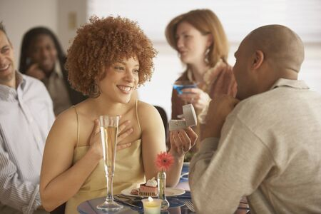 African man proposing to African woman at a restaurant, Richmond, Virginia, United States Stock Photo - 16070361