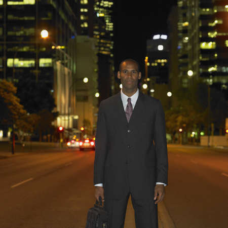 one mid adult man only: African businessman in urban setting at night, Perth, Australia LANG_EVOIMAGES