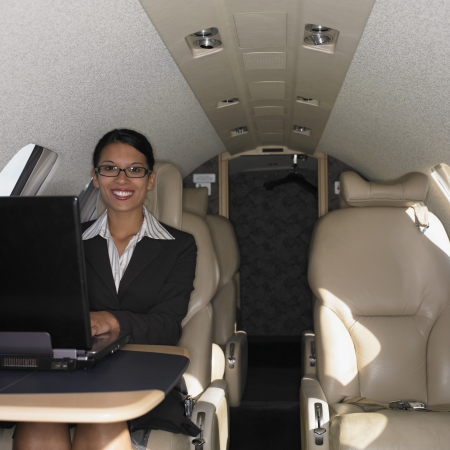 Businesswoman working on laptop inside airplane, Perth, Australia Stock Photo - 16090334
