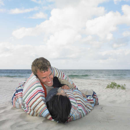 busselton: Couple wrapped in a blanket on the beach, Busselton, Australia