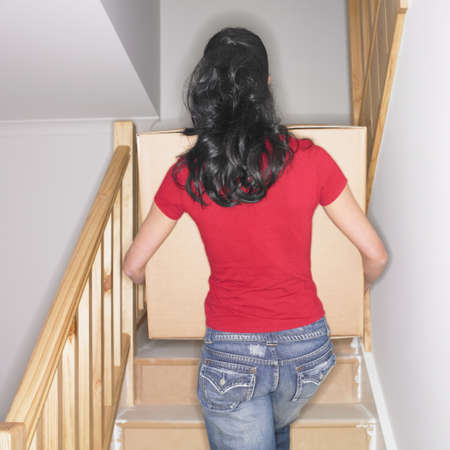 busselton: Woman carrying box up stairs in new house LANG_EVOIMAGES