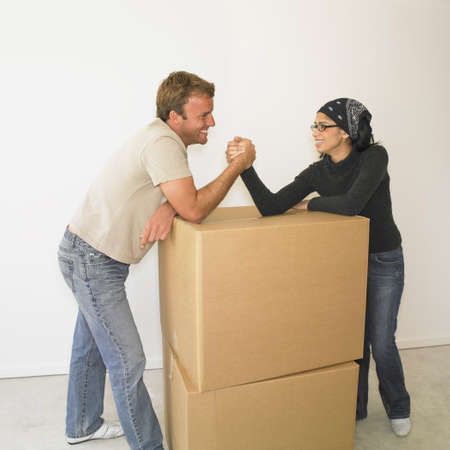 busselton: Couple arm wrestling on boxes in new house