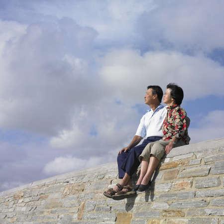man 40 50: Asian couple sitting on a wall, Perth, Australia