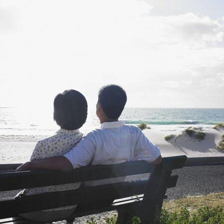mujer mirando el horizonte: Pareja sentada en un banco en la playa, Perth, Australia