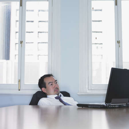wearying: Asian businessman slouched down in his chair