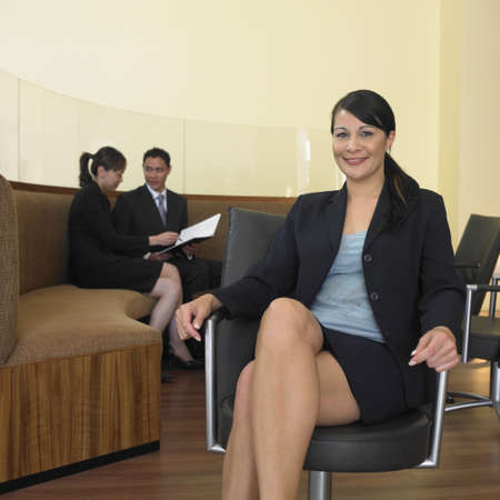 Businesswoman sitting with co-workers in background