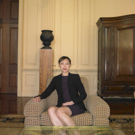 australian ethnicity: Asian businesswoman sitting in waiting area LANG_EVOIMAGES