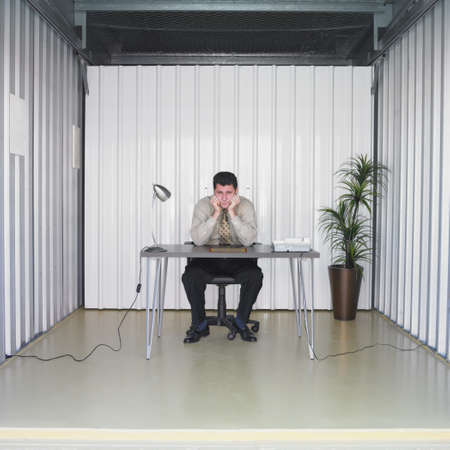 Businessman sitting at desk in storage unit Stock Photo - 16090407