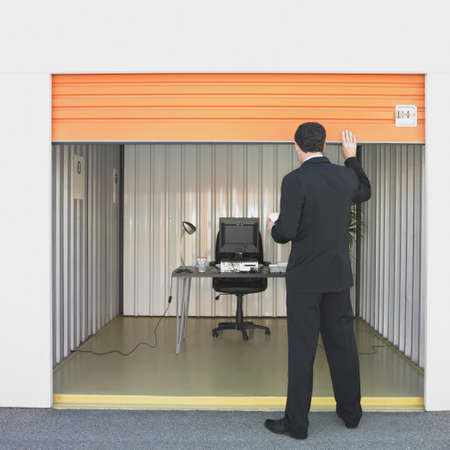 shutting: Businessman closing door of storage unit office
