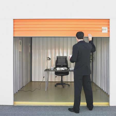 closing business: Empresario cierre de la puerta de la oficina de la unidad de almacenamiento LANG_EVOIMAGES