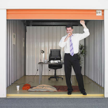 living thing: Businessman getting ready to sleep in storage unit office LANG_EVOIMAGES