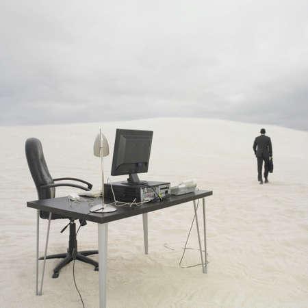 Businessman walking away from desk in the desert, Lancelin, Australia Stock Photo - 16090411