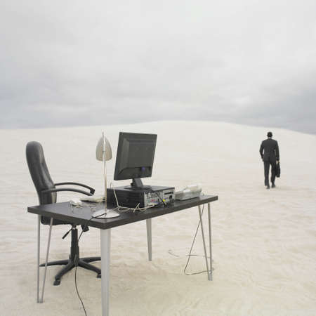 walking away: Businessman walking away from desk in the desert, Lancelin, Australia LANG_EVOIMAGES