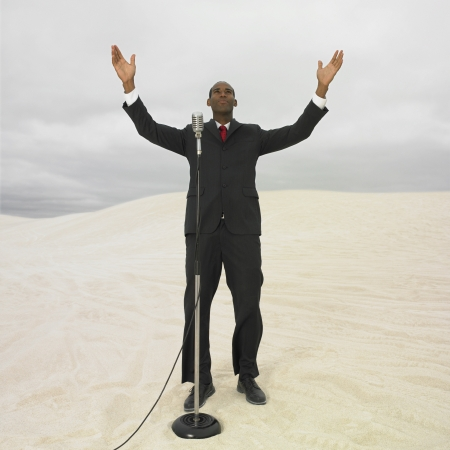 African businessman with microphone in desert, Lancelin, Australia Stock Photo - 16090412