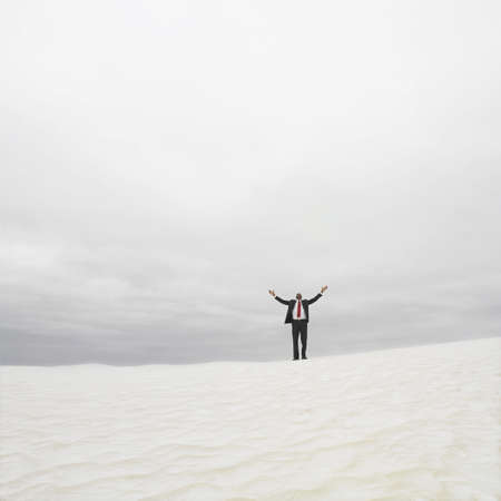 longshot: Businessman in the desert with his arms outstretched, Lancelin, Australia
