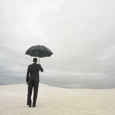 Businessman in the desert with an umbrella, Lancelin, Australia Stock Photo - 16090414