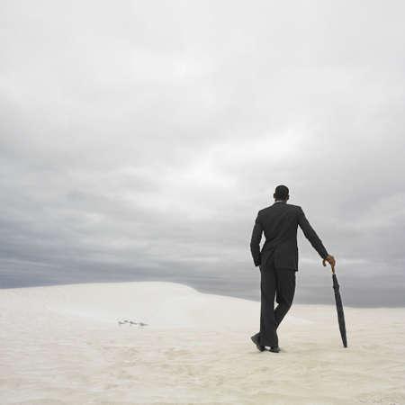 Businessman in the desert with an umbrella, Lancelin, Australia Stock Photo - 16090415