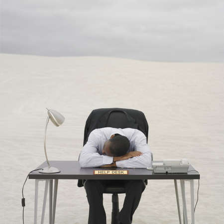 African businessman resting his head on help desk in the desert, Lancelin, Australia Stock Photo - 16090416