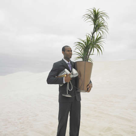 australian ethnicity: African businessman carrying plant and lamp in the desert, Lancelin, Australia LANG_EVOIMAGES