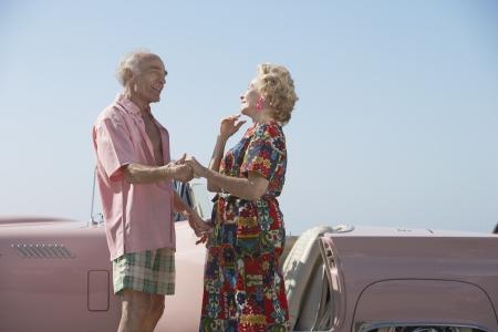 Senior couple next to a pink convertible Foto de archivo