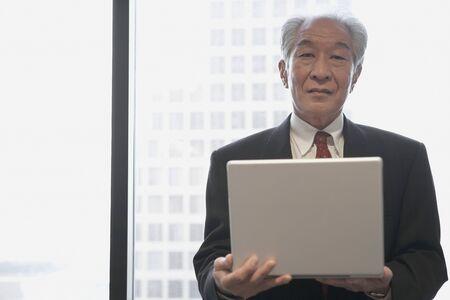 Senior Asian businessman with laptop next to window, Los Angeles, California, United States