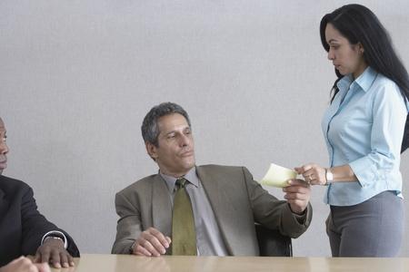 north western european descent: Businesswoman handing businessman a message