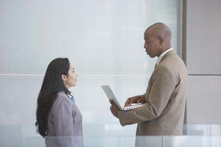 north western european descent: African businessman talking to Hispanic businesswoman