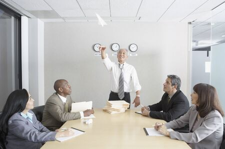 north western european descent: Senior Asian businessman throwing a paper airplane during a meeting