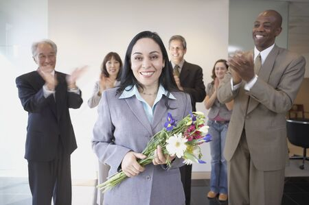 Businesswoman holding flowers while co-workers applaud Stock Photo - 16090450