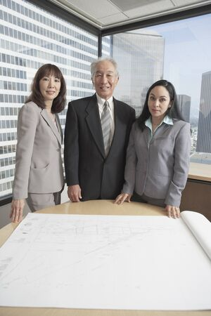 Senior Asian businessman and businesswomen looking at blueprints, Los Angeles, California, United States