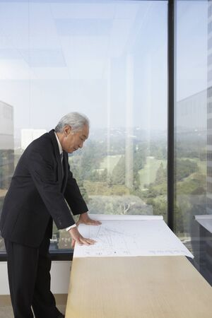 Senior Asian businessman looking at blueprints, Los Angeles, California, United States Stock Photo - 16090456