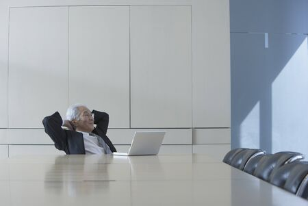 Senior Asian businessman sitting at head of conference table Stock Photo - 16090460