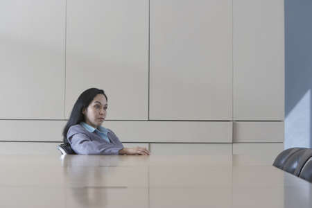 Hispanic businesswoman sitting at head of conference table Stock Photo - 16090463