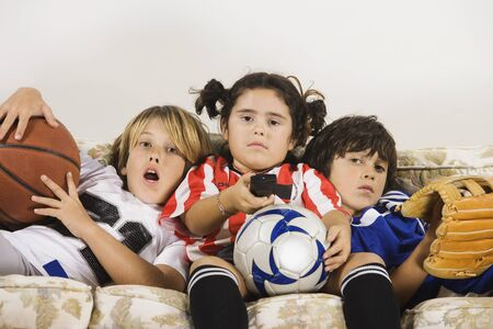 Group of children in sports gear watching television on the sofa 스톡 콘텐츠