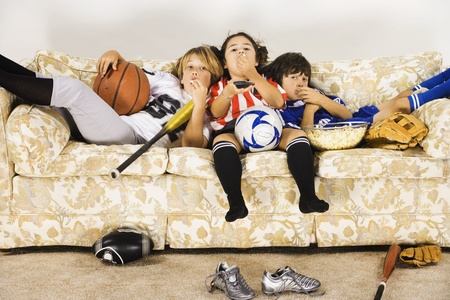 Group of children in sports gear watching television on the sofa Stock Photo