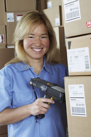 Female warehouse worker with barcode scanner Imagens
