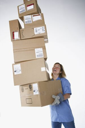 Studio shot of female warehouse worker carrying packages 写真素材