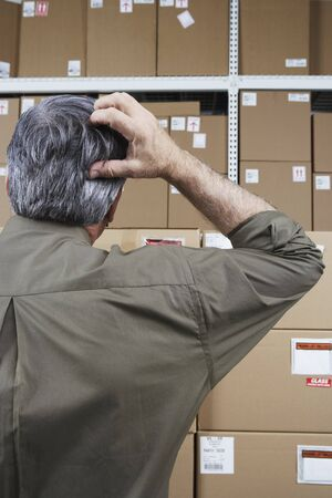 gaithersburg: Businessman in warehouse scratching his head LANG_EVOIMAGES