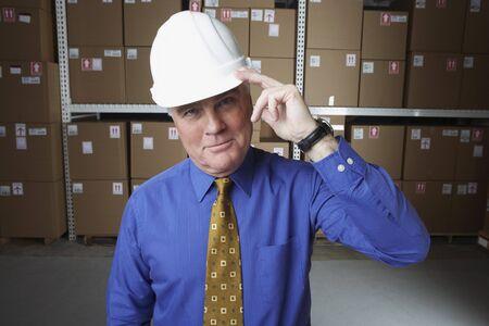 gaithersburg: Businessman wearing hard hat and saluting in warehouse