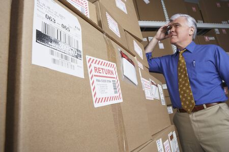 gaithersburg: Businessman in warehouse looking at returned packages LANG_EVOIMAGES