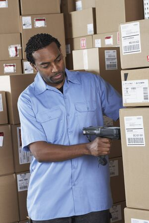 gaithersburg: Male African warehouse worker scanning packages LANG_EVOIMAGES