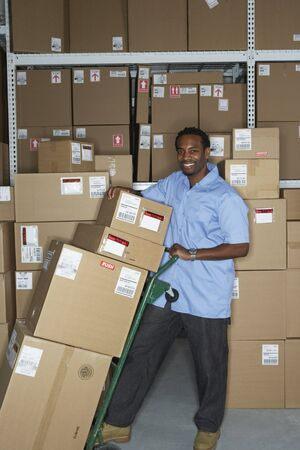 gaithersburg: Male African warehouse worker using hand truck LANG_EVOIMAGES