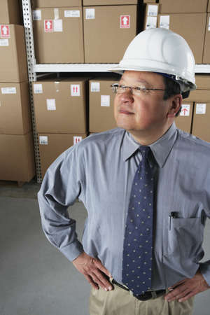 gaithersburg: Middle-aged Asian businessman wearing hard hat in warehouse
