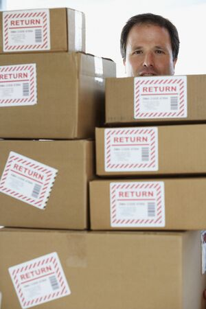 cardboard only: Studio shot of man behind returned packages