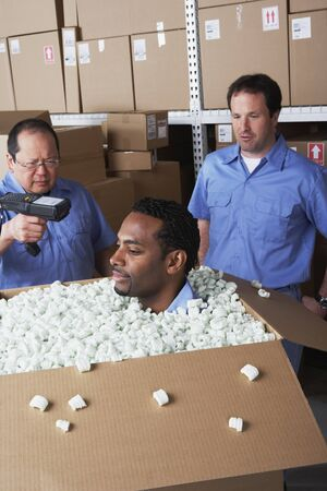 devilment: Three male warehouse workers joking around LANG_EVOIMAGES