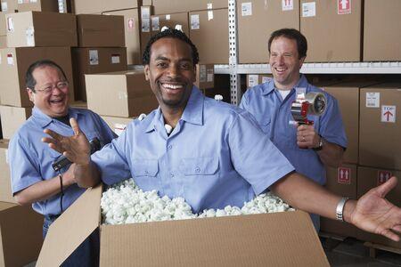mischeif: Three male warehouse workers joking around LANG_EVOIMAGES