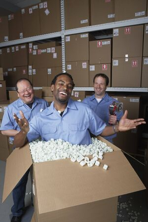 Three male warehouse workers joking around Stock Photo - 16090522