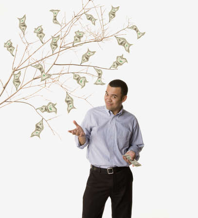 dollarbill: Studio shot of man with money growing on tree