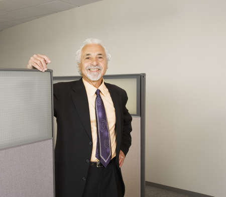 office cubicle: Senior businessman smiling in office cubicle LANG_EVOIMAGES