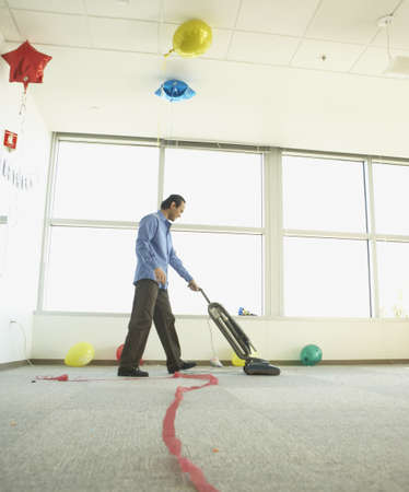 oriental rug: Man vacuuming after office party LANG_EVOIMAGES